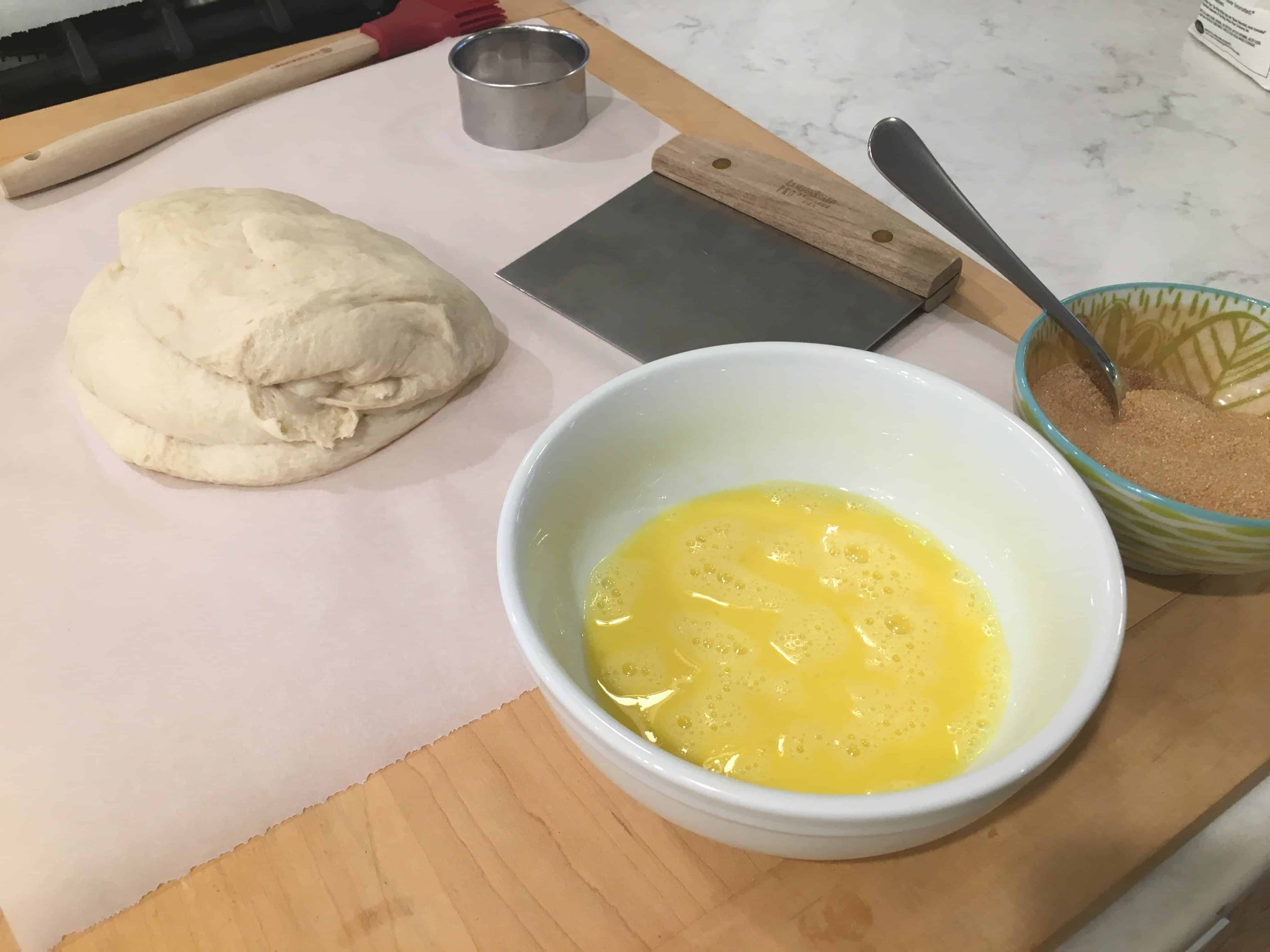 mound of dough on a table with a bowl of egg wash