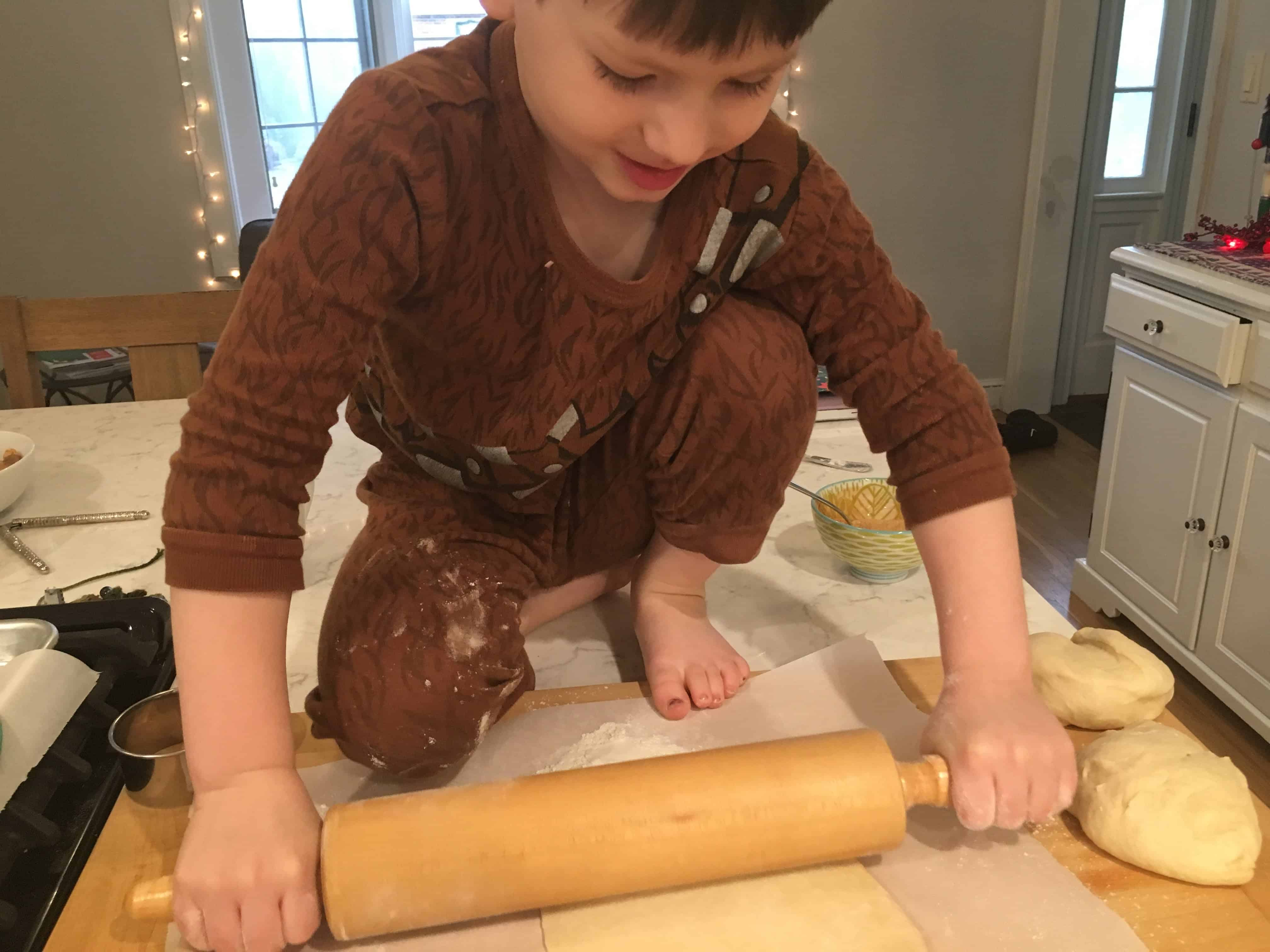 boy on a table rolling dough