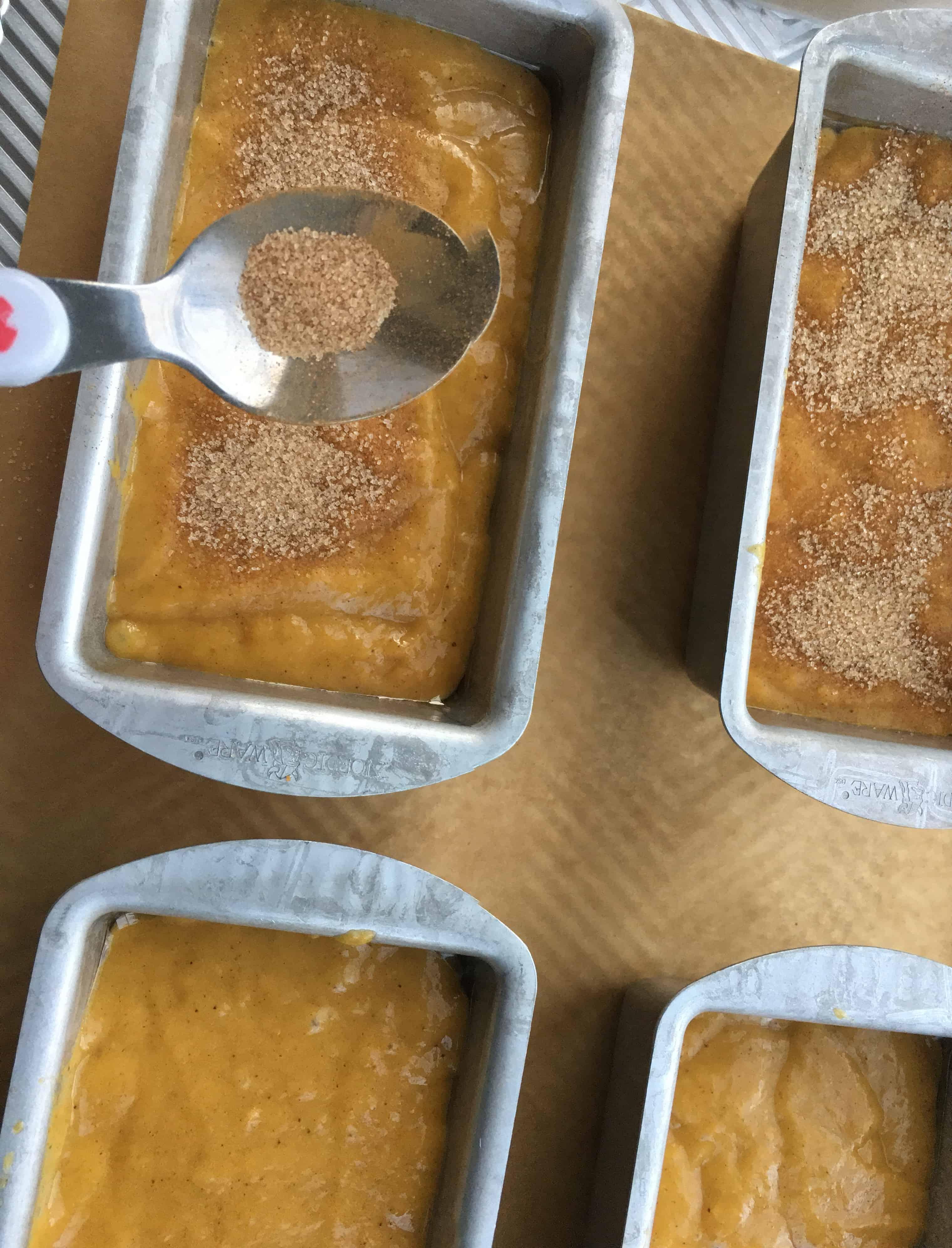 spooning brown sugar onto pumpkin bread before baking