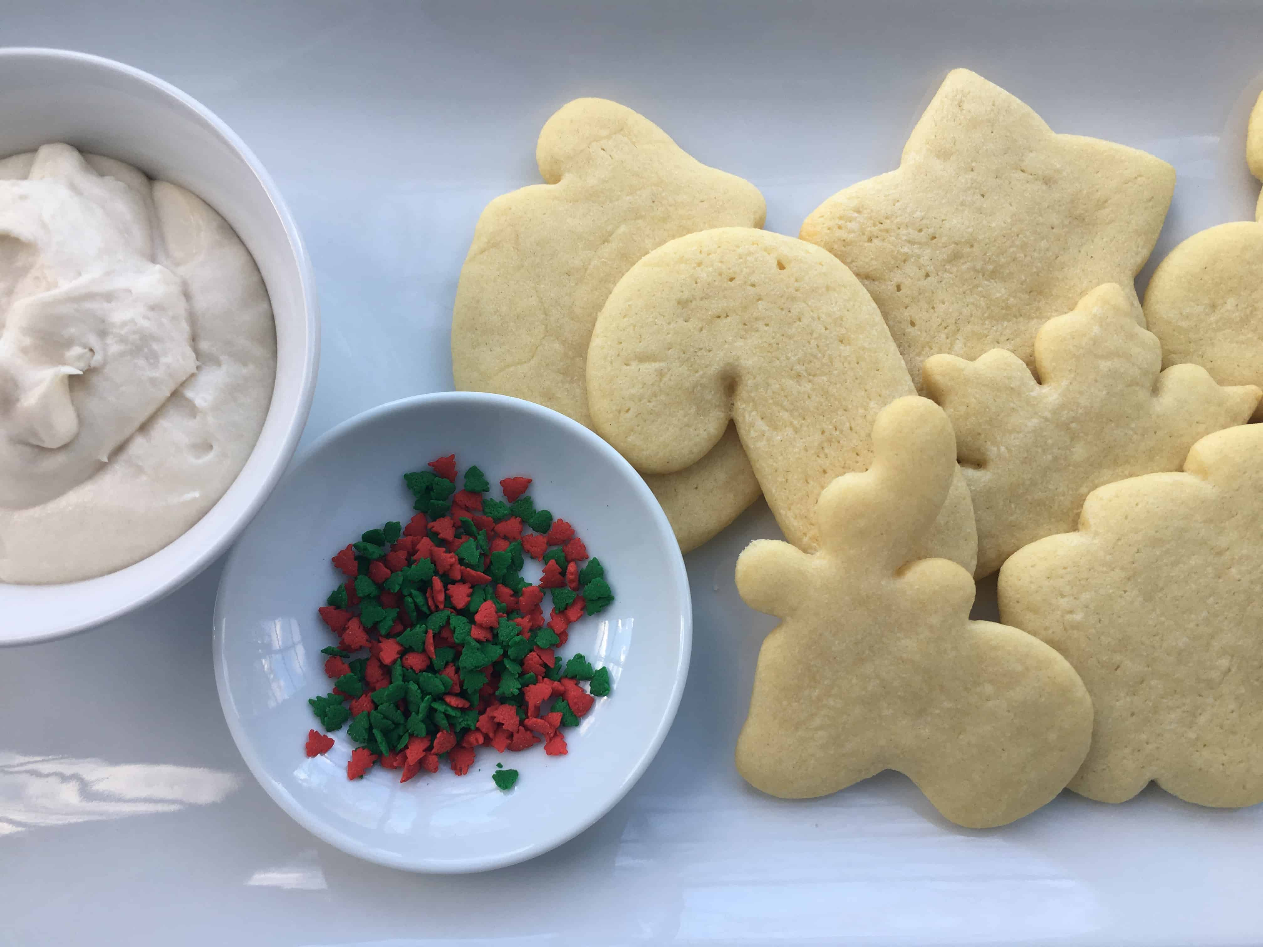 sugar cookies next to a bowl of sprinkles and frosting