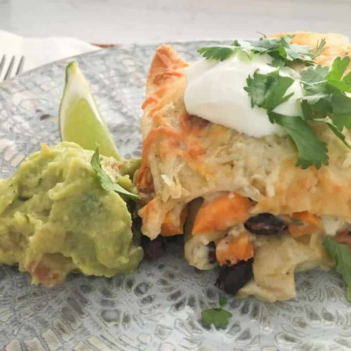 Maple Roasted Sweet Potato and Black Bean Enchiladas in a plate with guacamole