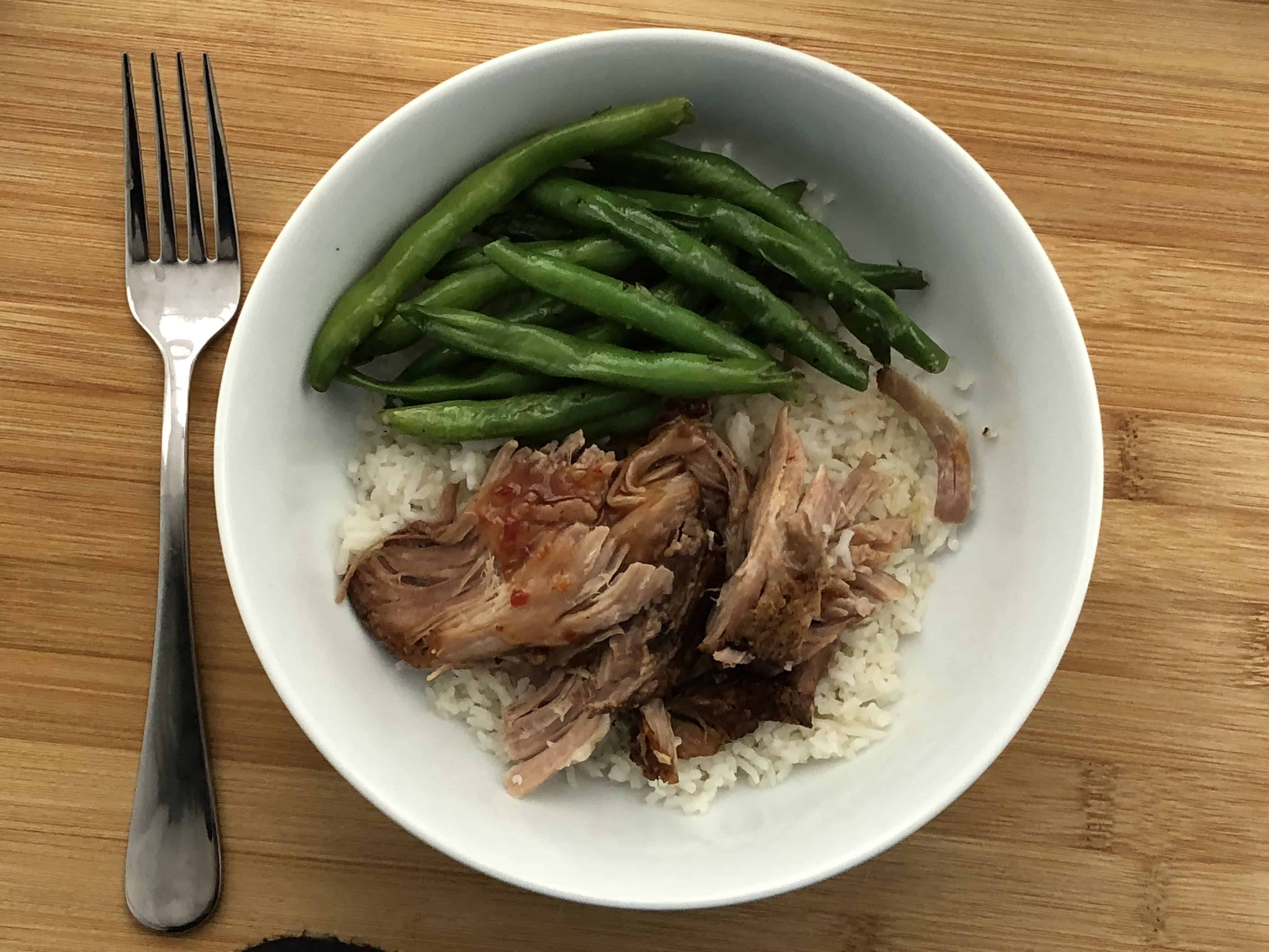 Slow Cooker Maple Bourbon BBQ Pork in a bowl with beans and rice