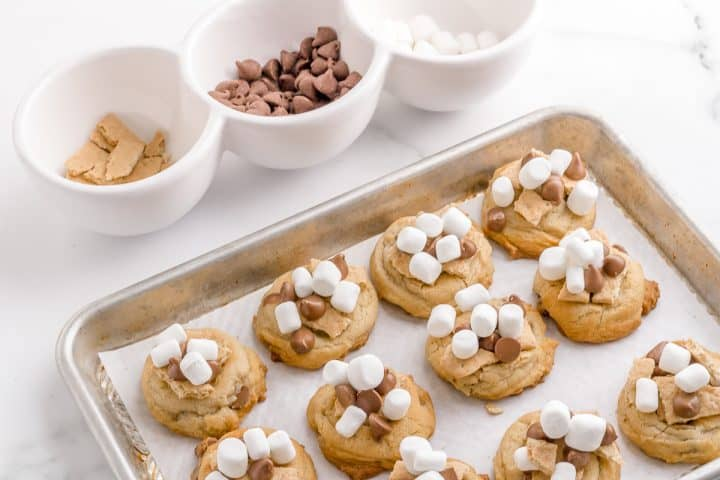 adding graham crackers chocolate and marshmallows to s'mores chocolate chip cookies
