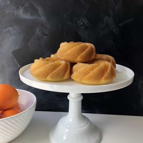 Orange Bundtlette Cakes on Cake Stand with Bowl of Oranges