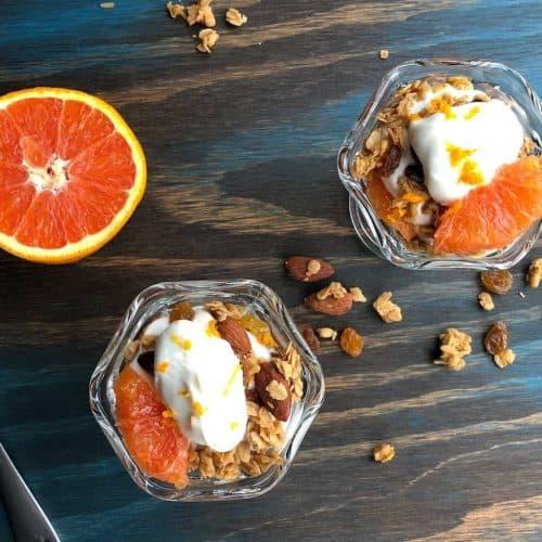 Two Orange Granola Parfaits on a table with half an orange