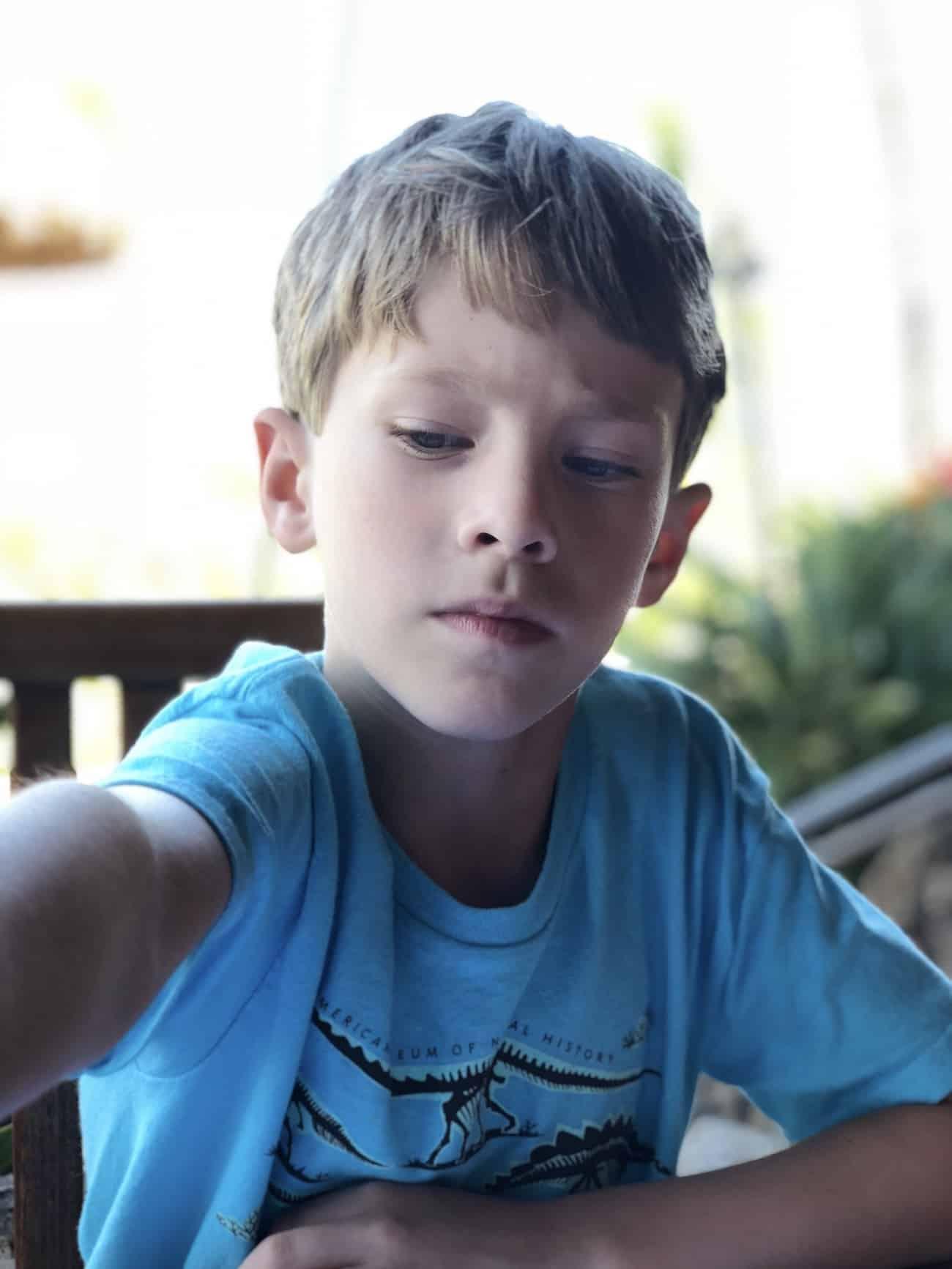 boy reaching in a chair