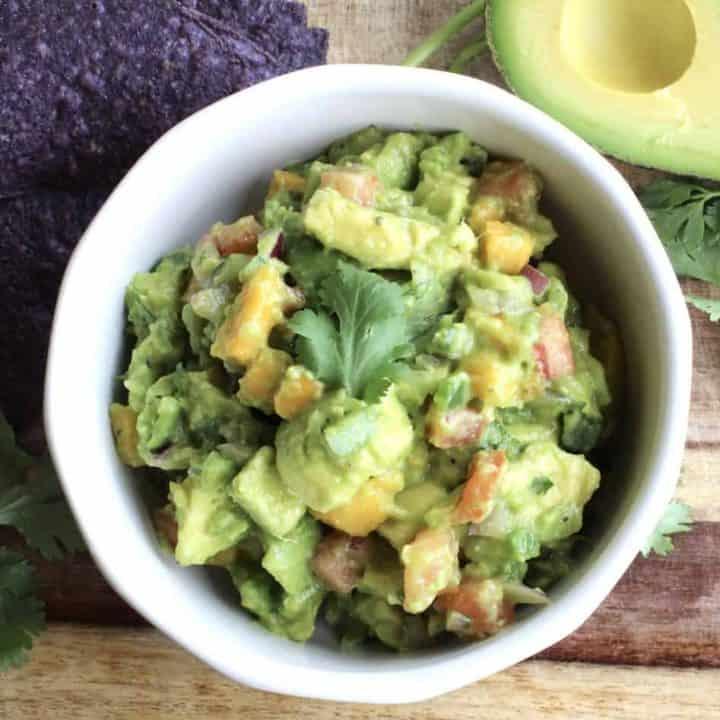 mango guacamole with half an avocado and blue corn chips