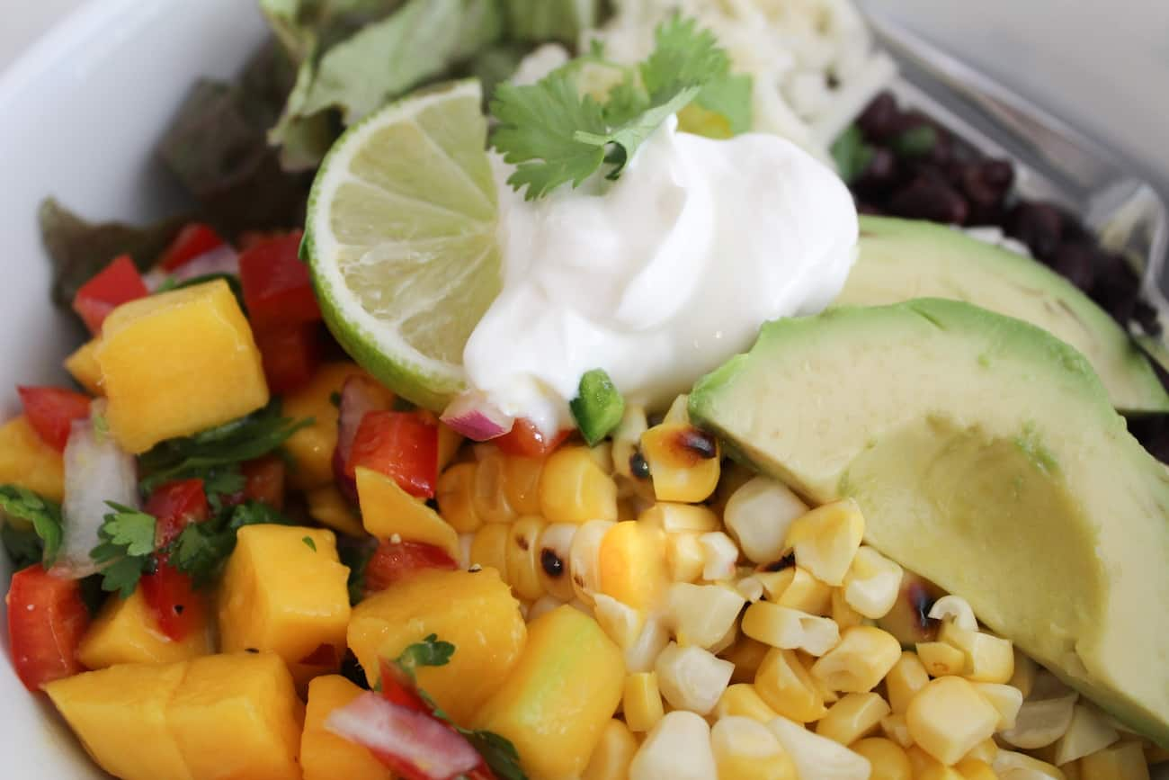 close up of a burrito bowl with avocado corn and lime