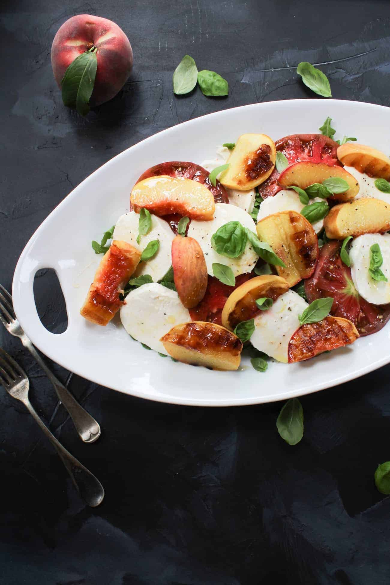 Grilled Peach Caprese Salad with Honey and Basil on a white plate