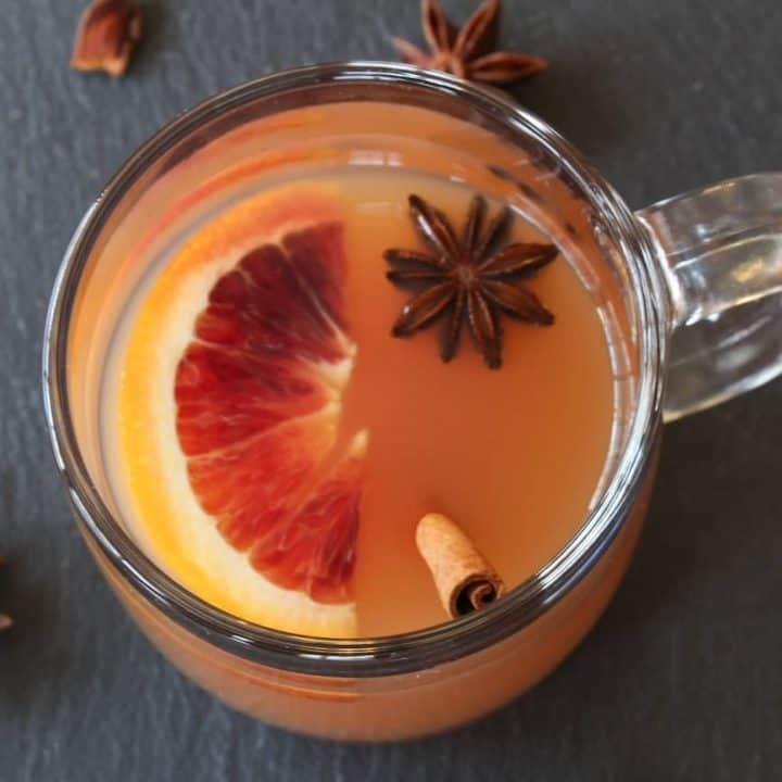 warm apple cider on slate with cinnamon stick
