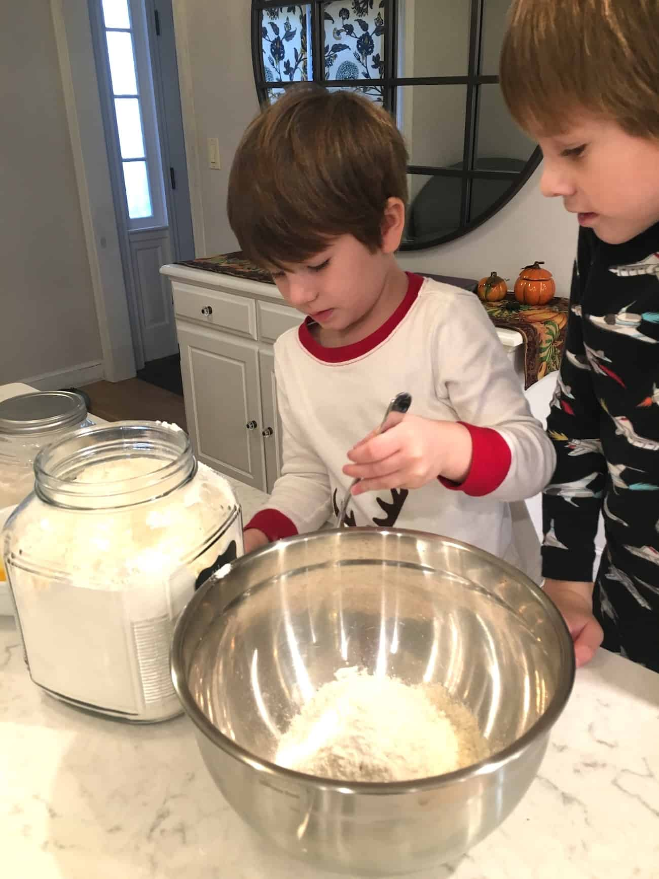 two boys measuring out dry ingredients in the kitchen