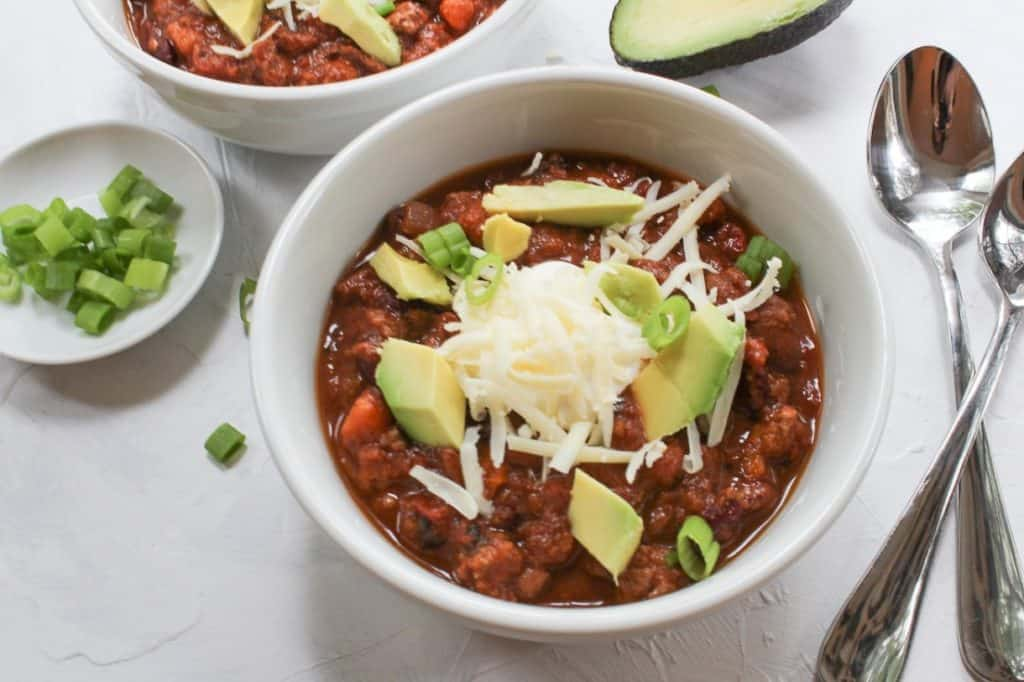 chili in a white bowl with diced avocado
