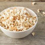 bowl of maple sea salt popcorn on gray wood