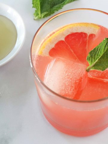 Sparkling Ruby Red Grapefruit Cocktail next to a bowl of honey