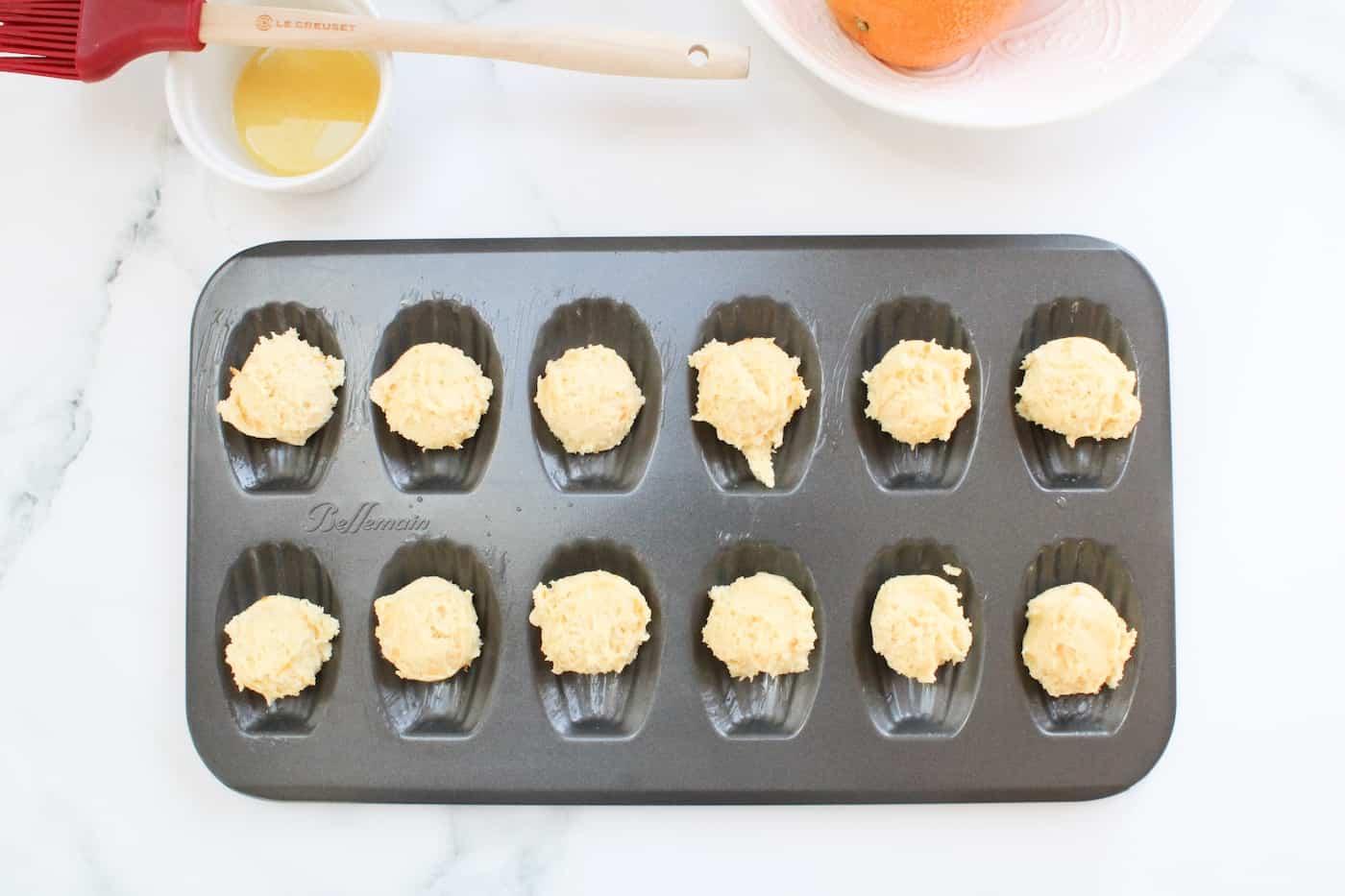 orange almond madeleine batter in prepared pan