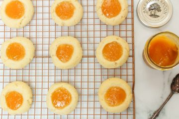 Macadamia Nut Thumbprint Cookies with Citrus and Passion Fruit Curd on a wire rack after baking