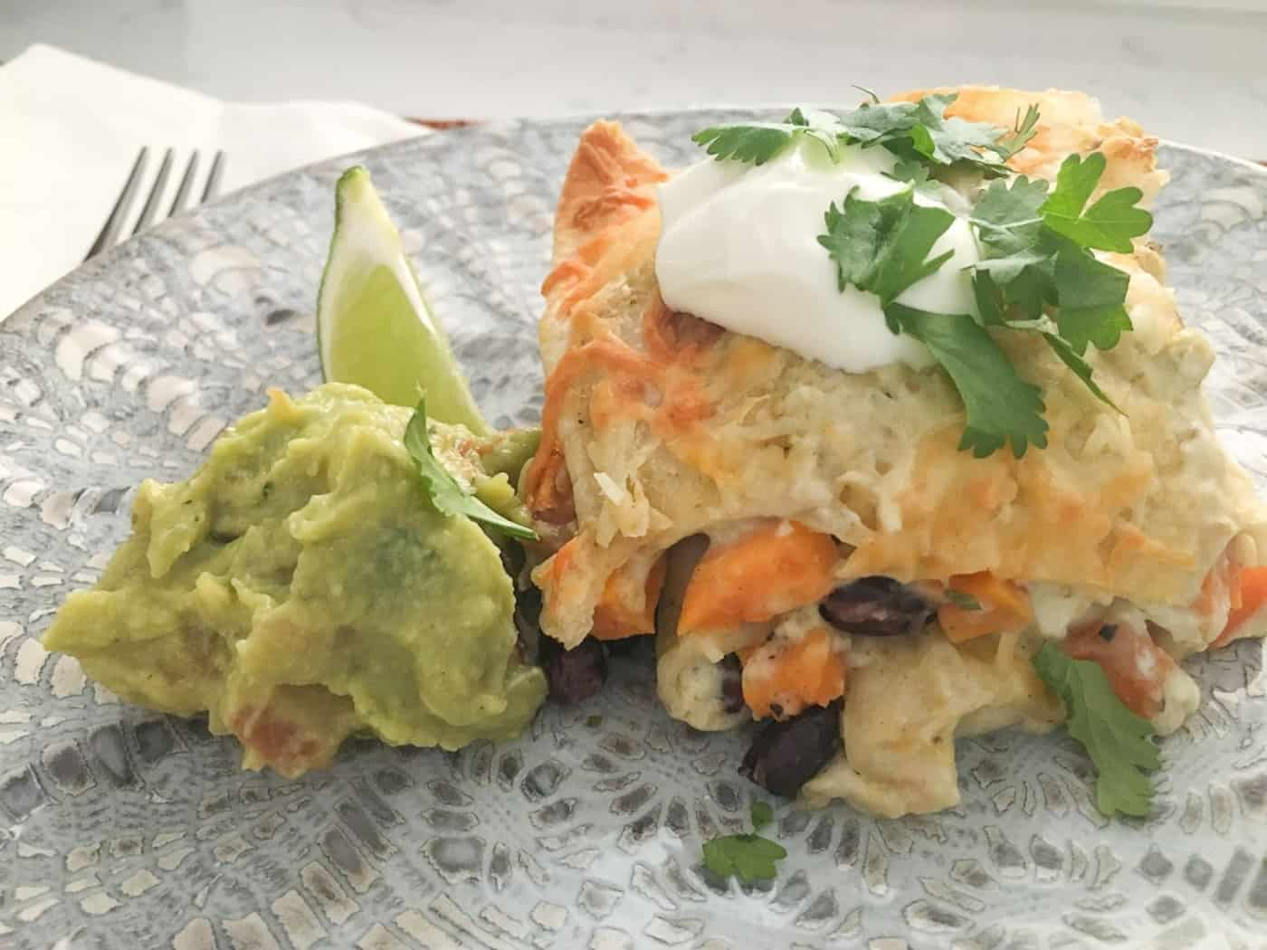 Portion of enchilada on a plate with guacamole