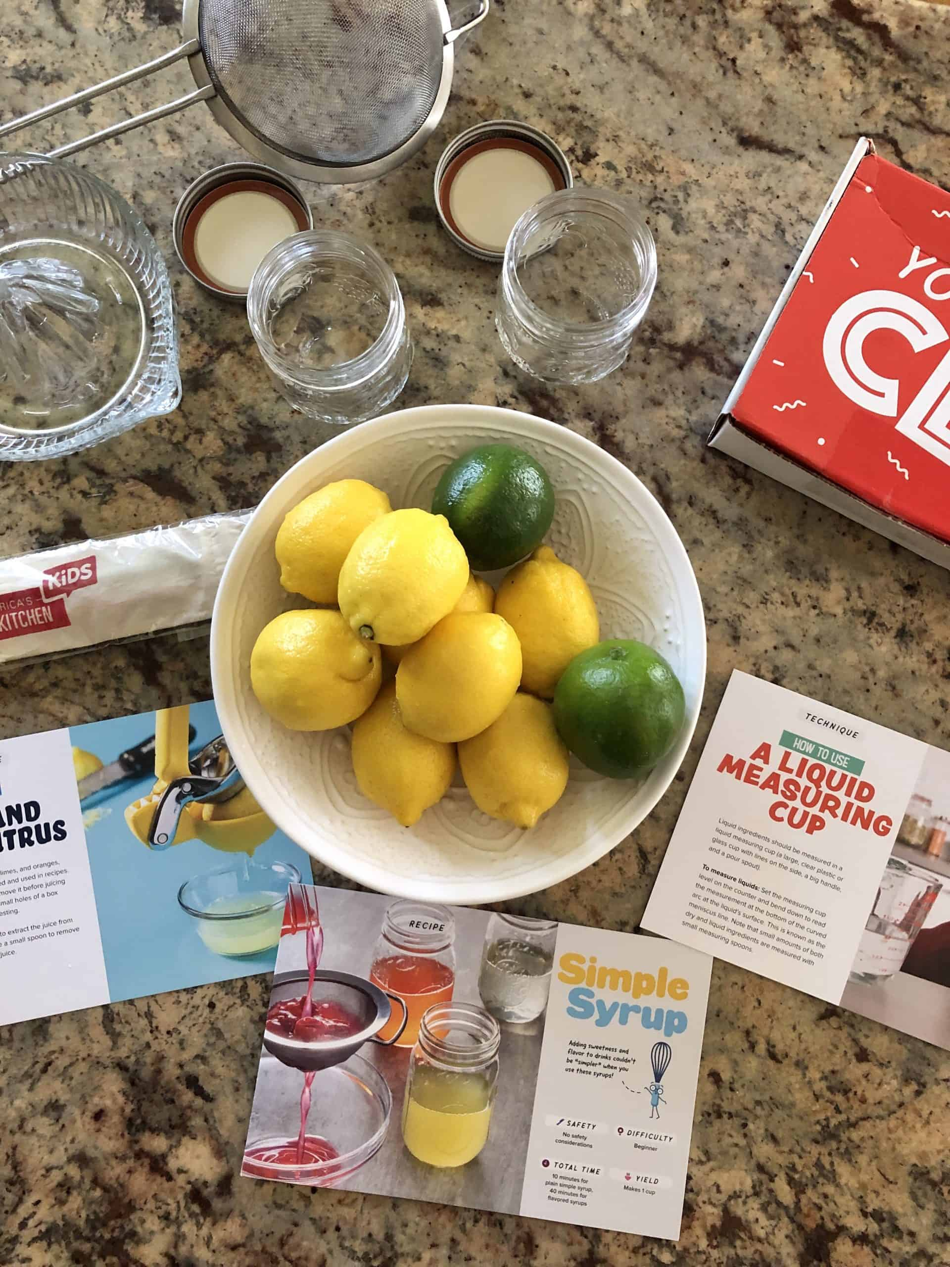 lemon and limes in a bowl with glasses and a sieve