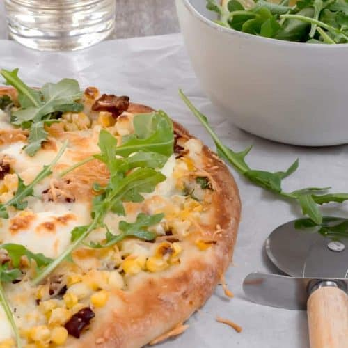 sweet corn and bacon pizza with salad and glass of white wine