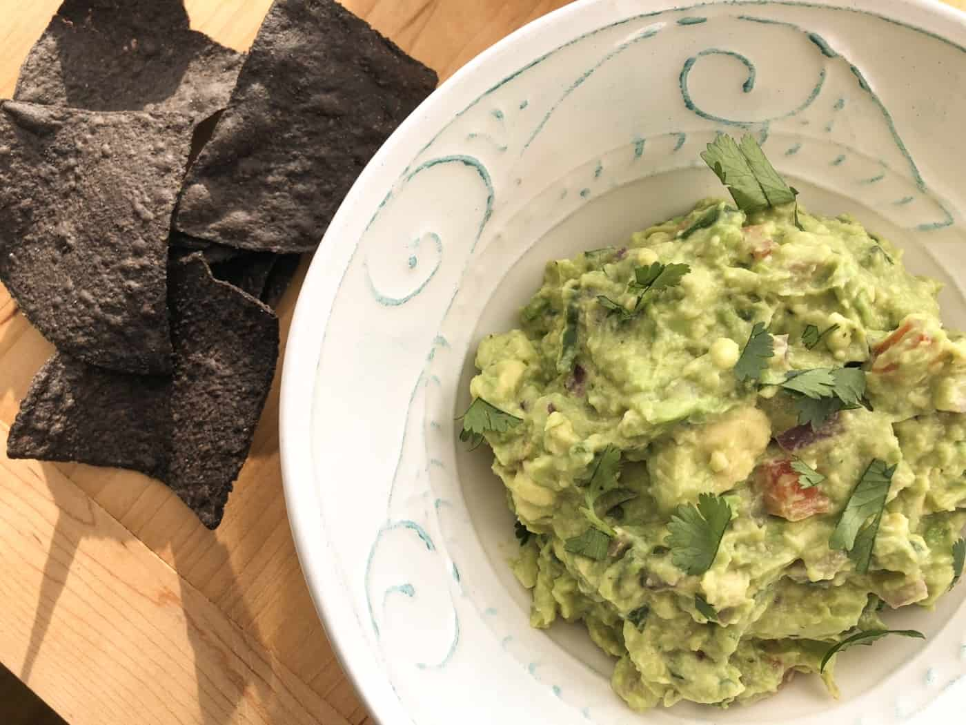 bowl of homemade guacamole with tortillas on the side