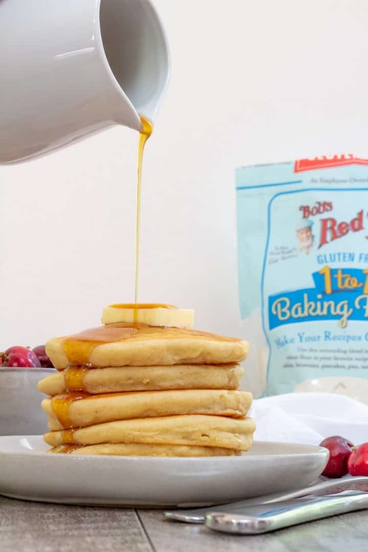 pouring maple syrup over best gluten free pancakes