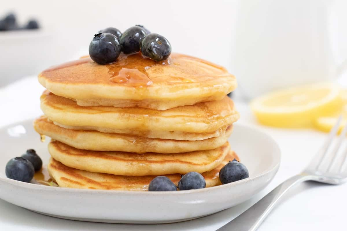 light and fluffy lemon pancakes with blueberries and maple syrup