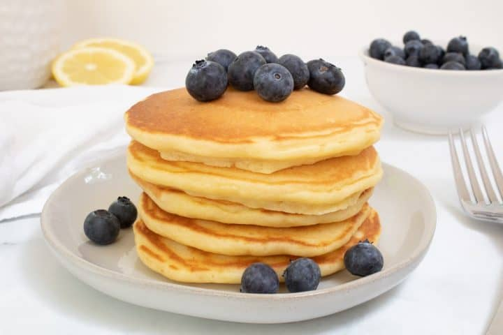 light and fluffy lemon pancakes on plate with fork and blueberries