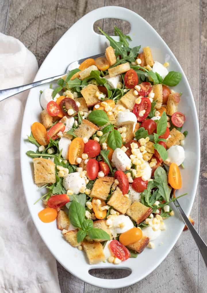 summer panzanella salad on white tray with serving forks