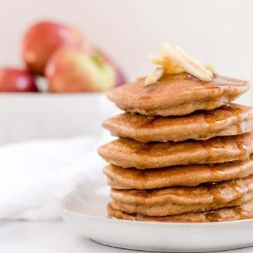 apple butter oatmeal pancakes on a plate with basket of apples