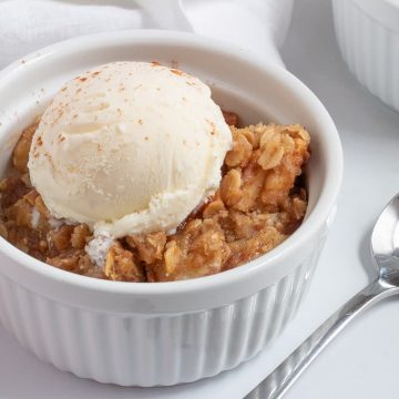 apple crisp in serving bowl with ice cream