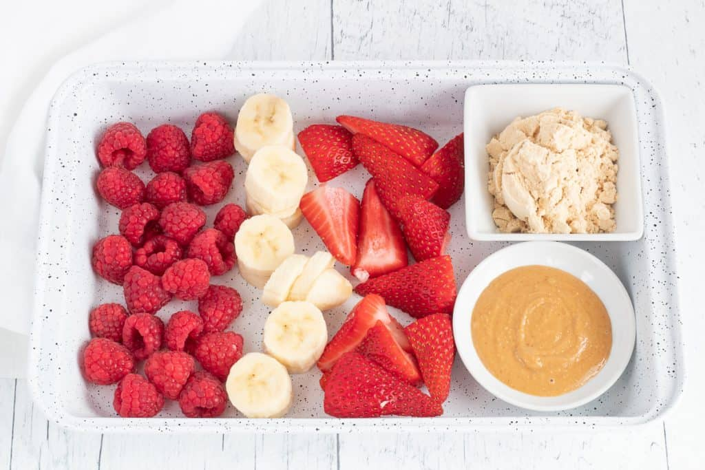 ingredients for healthy peanut butter and jelly smoothie on a tray