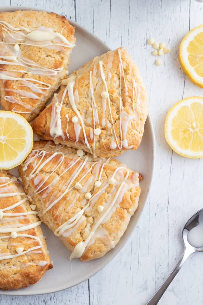 lemon white chocolate chip scones on white plate with spoon and lemon slices